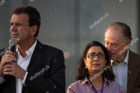 Nawal El Moutawakel, head of the International Olympic Committee's evaluation commission, center, listen to Brazil Olympic Committee President Carlos Arthur Nuzman, right, as Rio de Janeiro's mayor Eduardo Paes speaks during the inauguration of the Main Press Center (MPC) at the Rio 2016 Olympic Park in Rio de Janeiro, Brazil, . Rio de Janeiro will host the 2016 Olympic games