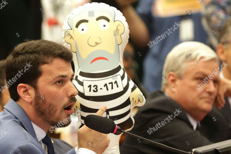 Marcelo Aro Opposition deputy Marcelo Aro, left, points to an inflatable doll in the likeness of former President Luiz Inacio Lula da Silva in prison garb, during the request for impeachment of Brazil's President Dilma Rousseff at the Chamber of Deputies, in Brasilia, Brazil, . Rousseff, who is battling the biggest recession in decades and a corruption probe that has circled in on members of her inner circle, is facing impeachment proceedings in Congress on allegations she violated fiscal laws