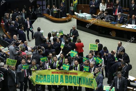 "Jose Eduardo Cardoso Brazil's Attorney General Jose Eduardo Cardozo, top left, presents the defense of Brazil's President Dilma Rousseff in the Chamber of Deputies, as opposition lawmakers hold signs that read in Portuguese ""Movement goodbye dear. It's over"" and ""Impeachment now"" in Brasilia, Brazil, . The lower chamber of Brazil's Congress began the debate on whether to impeach Rousseff, a question that underscores deep polarization in Latin America's largest country and most powerful economy. The crucial vote is slated for Sunday"