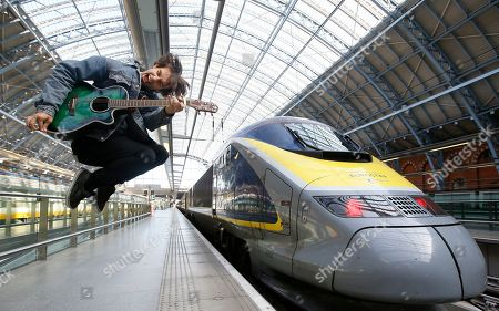 Champion London busker Alex James Ellison poses for the media by a Eurostar train at London St Pancras International terminal, . Alex will travel to Paris on Tuesday to promote London's busking talent after being awarded the Eurostar Prize in last year's Gigs competition