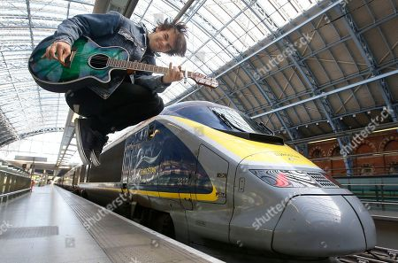 Stock Picture of Champion London busker Alex James Ellison poses for the media by a Eurostar train at London St Pancras International terminal, . Alex will travel to Paris on Tuesday to promote London's busking talent after being awarded the Eurostar Prize in last year's Gigs competition