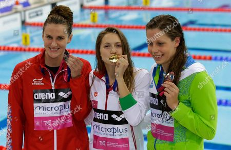 Hungary's gold medal winner Boglarka Kapas is flanked by silver medal winner Britain's Jazmin Carlin, left, and Slovenia's bronze medalist Tjasa Oder after the ceremony for the women's 800-meter freestyle final during the European Swimming Championships at the London Aquatics Centre in London