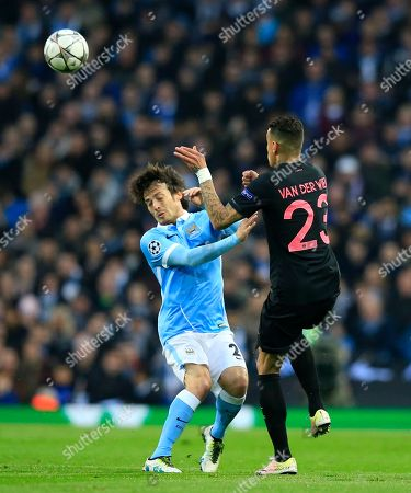 Manchester City's David Silva, left collides with PSG's Gregory van der Wiel as they chase a lose ball during the Champions League quarterfinal second leg soccer match between Manchester City and Paris Saint Germain at the City of Manchester stadium in Manchester, England