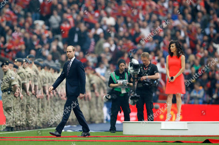 Britain's Prince William walks on the pitch as singer Karen Harding, right, holds her microphone before the English FA Cup final soccer match between Manchester United and Crystal Palace at Wembley stadium in London