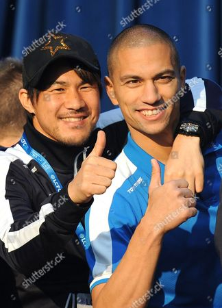 Leicester City's Shinji Okazaki, left, and Gokhan Inler gesture to fans during celebrations at Victoria Park, Leicester, England, during the victory parade after winning the English Premier league title