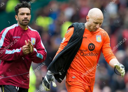 Aston Villa's goalkeeper Brad Guzan, left, and Kieran Richardson walk from the pitch as their team is relegated from the English Premier League after being defeated 1-0 by Manchester United at Old Trafford Stadium, Manchester, England