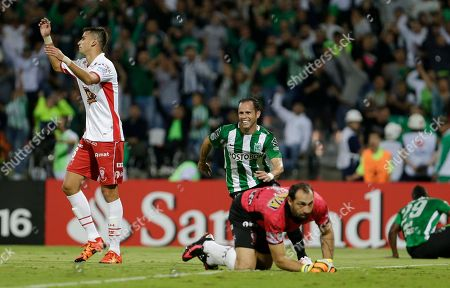 Alejandro Guerra, Mario Risso, Marcos Diaz Alejandro Guerra of Colombia's Atletico Nacional, back, celebrates scoring his side's 3rd goal as Marcos Diaz goalkeeper of Argentina's Huracan lies on the pitch and Huracan's defender Mario Risso left, gestures during a Copa Libertadores round of sixteen second leg soccer match in Medellin, Colombia
