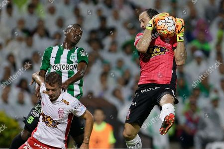 Marcos Diaz, Marlos Moreno, Luciano Balbi Marcos Diaz goalkeeper of Argentina's Huracan intercepts a shot as his teammate Luciano Balbi, bottom left, and Marlos Moreno of Colombia's Atletico Nacional go for a header during a Copa Libertadores round of sixteen second leg soccer match in Medellin, Colombia