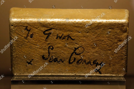 "A fake gold bar signed by Sean Connery for Gwen, the daughter of the dresser in the James Bond film ""Goldfinger"" is displayed during a press presentation of the exhibition ""The Designing 007: Fifty Years of Bond Style"" at the Grande Halle de la Villette in Paris, France"