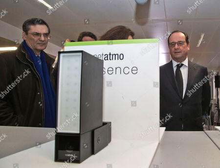 """French President Franocis Hollande, right, and French politician Patrick Devedjian, left, listening speaks as he visits a tech company in Boulogne-Billancourt, outside Paris, . French president says the Panama revelations are """"good news"""" because it will help the state to recover money from people who have committed tax evasion"""