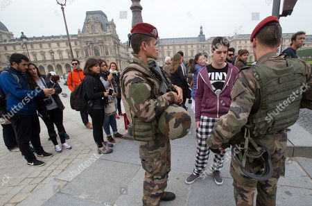 Thomas Williams, from Argentina, center, asks his way to French soldiers corporal Thomas, left, and staff sergeant Baudouin, at the Louvre museum in Paris, . The Associated Press was allowed to accompany a platoon from the French army's 1st Parachute Hussar Regiment as it demonstrated a typical patrol at the Louvre Museum in Paris. The AP was allowed only on condition that the soldiers involved be identified by their rank and first name