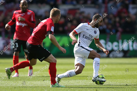 Paris Saint Germain's forward Lucas Moura of Brazil, right, challenges for the ball with Guingamp's defender Lars Jacobsen of Denmark during their French League One soccer match, in Guingamp, western France. Paris SG 2-0