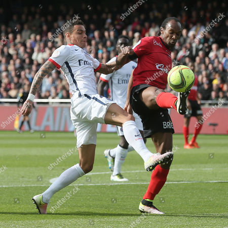 Paris Saint Germain's defender Gregory Van Der Wiel, left, challenges for the ball with Guingamp's defender Jeremy Sorbon during their French League One soccer match, in Guingamp, western France