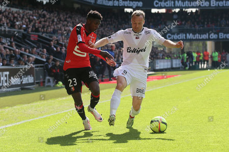 Stock Photo of Rennes' Ousmane Dembele, left, challenges for the ball with Guingamp's Lars Jacobsen during his French League One soccer match against Guingamp, in Rennes, western France
