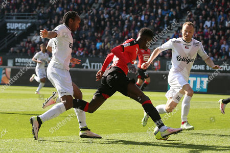 Stock Image of Rennes' Ousmane Dembele, center, dribbles the ball against Guingamp's Jeremy Sorbon, left, and Lars Jacobsen during their French League One soccer match, in Rennes, western France