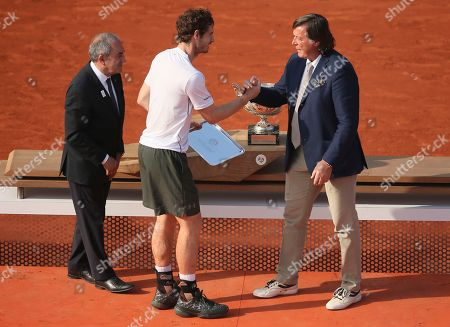 Britain's Andy Murray, center, shakes hands with former Italian tennis ace Adriano Panatta during their final match of the French Open tennis tournament at the Roland Garros stadium, in Paris. At left is Jean Gachassin, head of the French tennis federation