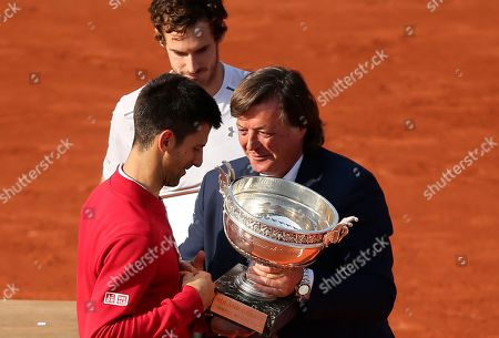 Former Italian tennis ace Adriano Panatta, right, gives the cup to Serbia's Novak Djokovic as Britain's Andy Murray looks on after the final match of the French Open tennis tournament at the Roland Garros stadium, in Paris