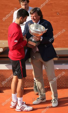 Former Italian tennis ace Adriano Panatta gives the cup to Serbia's Novak Djokovic after the final match of the French Open tennis tournament at the Roland Garros stadium, in Paris