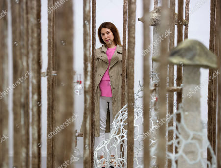Anicka Yi, born in Seoul, South Korea and now living in New York, stands behind her installation 'When Species Meet Part 1' during the press preview at the exhibition 'Jungle Stripe' in the Fridericianum museum in Kassel, Germany, . The exhibition starts on May 29, 2016 and lasts until Sept. 9, 2016