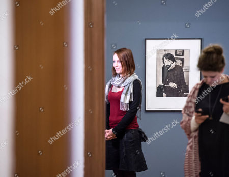 Visitors walk around a photo of Paul McCartney made by Linda McCartney during the press preview at the exhibition 'Sixties' by Linda McCartney in the Avant-garde House of Art in Apolda, Germany, . The exhibition presents the works of the photographer Linda McCartney and offers intimate insight into the private life of the McCartneys, the Beatles and other artists. The exhibition starts on April 10, 2016 and lasts until June 19, 2016