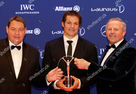 Richie McCaw, center, captain of the All Blacks, and former rugby player Sean Fitzpatrick, right, and New Zealand's head coach Steve Hansen hold a Laureus Team of the Year award at the Laureus World Sports Awards in Berlin, Germany