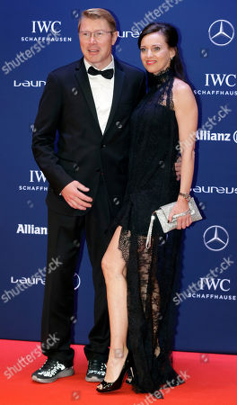 Mika Hakkinen, left, and his partner Marketa Remesova, right, pose for photos as they arrive for the Laureus World Sports Awards in Berlin, Germany