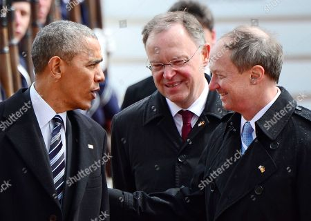 U.S. President Barack Obama, left, talks to John B. Emerson, US ambassador to Germany, right, and Stephan Weil, governor of German state of Lower Saxony, center, upon his arrival at the airport in Hannover, northern Germany, . Obama is on a two-day official visit to Germany
