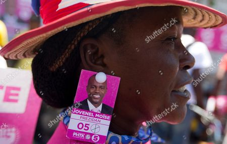 A supporter of presidential candidate Jovenel Moise, from the PHTK political party, has a picture of Moise on her earing, during a protest to demand the second round presidential election in Port-au-Prince, Haiti, . Haiti had been scheduled to hold a presidential and legislative second runoff election on Jan. 24, but the now-splintered provisional electoral council canceled it for a second time amid protests and suspicion that the first round was marred by widespread fraud favoring Moise, the chosen candidate of former President Michel Martelly
