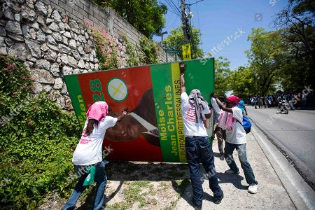 Supporters of presidential candidate Jovenel Moise, from the PHTK political party, tear down a campaign poster of former candidate Moise Jean Charles, during a protest to demand the second round presidential election in Port-au-Prince, Haiti, . Haiti had been scheduled to hold a presidential and legislative second runoff election on Jan. 24, but the now-splintered provisional electoral council canceled it for a second time amid protests and suspicion that the first round was marred by widespread fraud favoring Moise, the chosen candidate of former President Michel Martelly