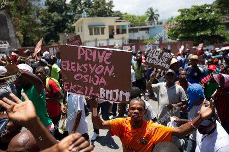 """A supporter of presidential candidate Jovenel Moise, from the PHTK political party, holds up a sign that reads in Creole """"Prive, election or exile,"""" referring to provisional president Jocelerme Privert, during a protest to demand the second round presidential election in Port-au-Prince, Haiti, . Haiti had been scheduled to hold a presidential and legislative second runoff election on Jan. 24, but the now-splintered provisional electoral council canceled it for a second time amid protests and suspicion that the first round was marred by widespread fraud favoring Moise, the chosen candidate of former President Michel Martelly"""