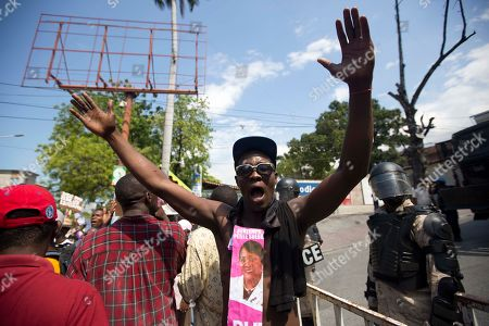 A supporter of presidential candidate Jovenel Moise, from the PHTK political party, chants anti-government slogans during a protest to demand the second round presidential election in Port-au-Prince, Haiti, . Haiti had been scheduled to hold a presidential and legislative second runoff election on Jan. 24, but the now-splintered provisional electoral council canceled it for a second time amid protests and suspicion that the first round was marred by widespread fraud favoring Moise, the chosen candidate of former President Michel Martelly