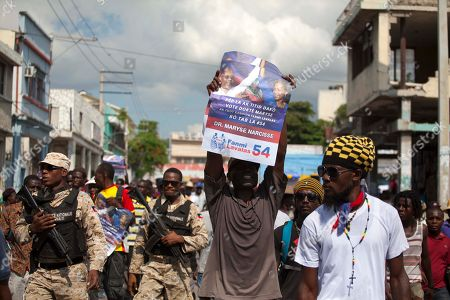 A supporter of former presidential candidate Maryse Narcisse from Fanmi Lavalas political party holds up a campaign poster during a protest march to the parliament building in Port-au-Prince, Haiti, . Haiti's provisional President Jocelerme Privert provisional administration recently appointed a commission to verify contested elections held last year that many suspect were tainted by rampant dirty tricks benefiting Tet Kale, the party of previous President Michel Martelly