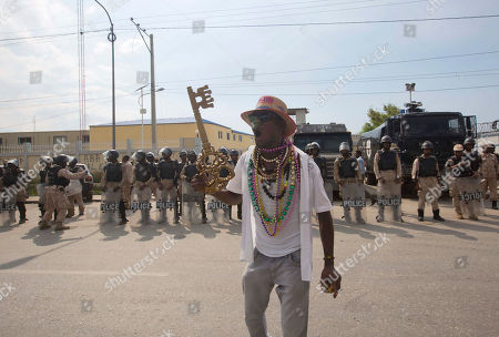 """A supporter of former presidential candidate Maryse Narcisse from the Fanmi Lavalas political party holds up a large key while stating """"The key of the national palace is for Maryse Narcisse,"""" in front of the parliament building, during a demonstration in Port-au-Prince, Haiti, . Haiti's provisional President Jocelerme Privert provisional administration recently appointed a commission to verify contested elections held last year that many suspect were tainted by rampant dirty tricks benefiting Tet Kale, the party of previous President Michel Martelly"""