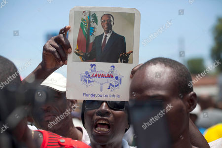 A supporter of former presidential candidate Maryse Narcisse from Fanmi Lavalas political party holds up a picture of former president Jean Bertrand Aristide, while they march to the parliament building in Port-au-Prince, Haiti, . Haiti's provisional President Jocelerme Privert provisional administration recently appointed a commission to verify contested elections held last year that many suspect were tainted by rampant dirty tricks benefiting Tet Kale, the party of previous President Michel Martelly