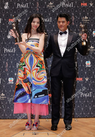 """Jessie Li, Aaron Kwok Chinese actress Jessie Li, left, and Hong Kong actor Aaron Kwok pose after winning the Best Actress award and the Best Actor award for their movie """"Port of Call"""" during the Hong Kong Film Awards in Hong Kong"""