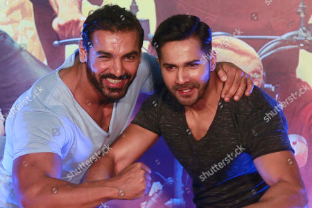 Bollywood actors Varun Dhawan right, along with John Abraham pose for a picture during the trailer launch of their upcoming film Dishoom in Mumbai, India