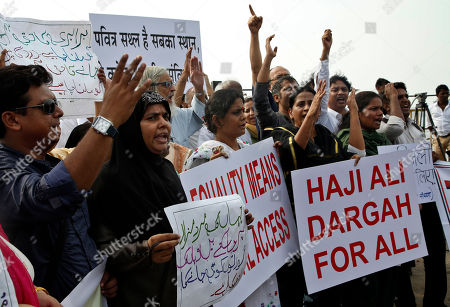 People shout slogans to support women's rights activist, Trupti Desai, as she protests to oppose the ban on women entering the Muslim Shrine of Haji Ali Dargah, in Mumbai, India, . Desai, who asserts that women have an equal right to pray, has earlier campaigned successfully to ensure Hindu women get entry into temples that had traditionally never allowed women inside