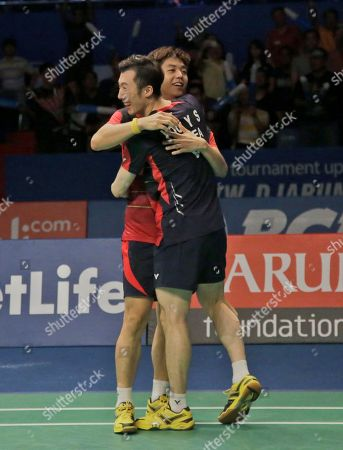 South Korea's Yoo Yeong-seong, front, and Lee Yong-dae celebrate after defeating China's Chai Biao and Hong Wei during their men's doubles final match at the Indonesia Open badminton tournament at Istora Stadium in Jakarta, Indonesia