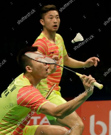 China's Hong Wei, bottom, and Chai Biao compete against South Korea's Lee Yong-dae and Yoo Yeong-seong during their men's doubles final match at the Indonesia Open badminton tournament at Istora Stadium in Jakarta, Indonesia