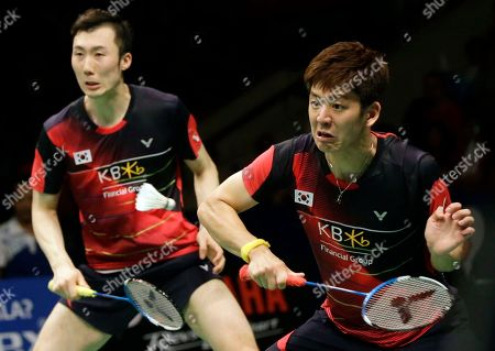South Korea's Lee Yong-dae, right, and Yoo Yeong-seong compete against China's Chai Biao and Hong Wei during their men's doubles final match at the Indonesia Open badminton tournament at Istora Stadium in Jakarta, Indonesia
