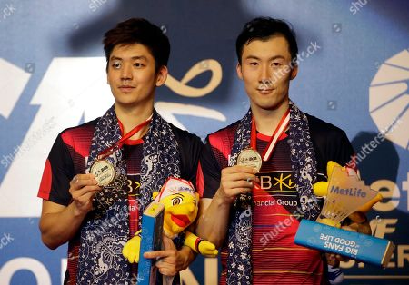 South Korea's Lee Yong-dae, left, and Yoo Yeong-seong shows their medal on the podium as they pose for photographers after defeating China's Chai Biao and Hong Wei in their men's doubles final match at the Indonesia Open badminton tournament at Istora Stadium in Jakarta, Indonesia