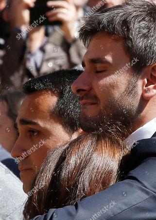 Alessandro Di Battista, right, Carla Ruocco and Luigi Di Maio, embrace during the funeral of the co-founder of Italy's 5-star Movement Gianroberto Casaleggio outside Santa Maria delle Grazie Basilica, in Milan, Italy