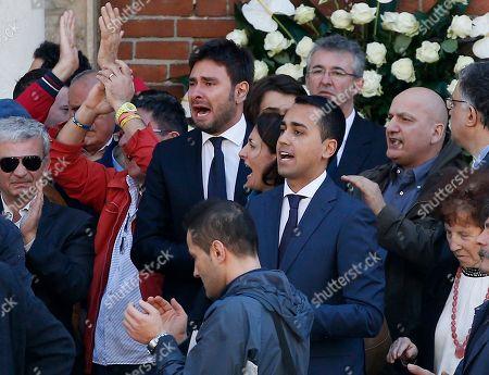 Alessandro Di Battista, left, with Carla Ruocco and Luigi Di Maio, right, applaude during the funeral of the co-founder of Italy's 5-star Movement Gianroberto Casaleggio outside Santa Maria delle Grazie Basilica, in Milan, Italy