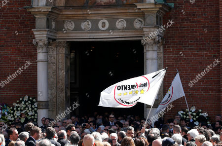 People wave flags during the funeral of the co-founder of Italy's 5-star Movement Gianroberto Casaleggio outside Santa Maria delle Grazie Basilica, in Milan, Italy