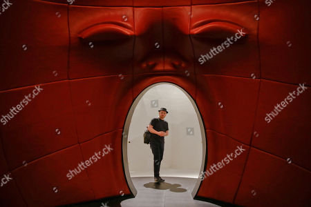 A visitor admires the installation 'Intro' by architect Fabio Novembre, part of the 'Fuori Salone' exhibitions during the Design Week, in Milan, Italy