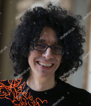 Italian musician Giovanni Allevi smiles as he poses after a news conference in Milan, Italy