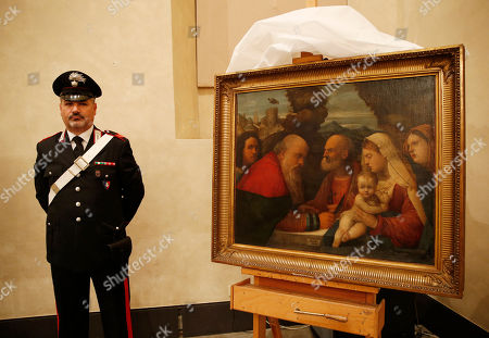"""An Italian Carabinieri paramilitary police officer stands next to a painting """"Circumcision of Jesus at Temple"""", attributed to early Renaissance painter Girolamo dai Libri, during a press conference on recovered paintings seized by the Nazis in 1944 in Camaiore near Lucca, Italy, at the Brera Art Gallery, in Milan, Italy, . The paintings were seized from the Italian villa of Prince Felix Bourbon-Parma, then Prince of Luxembourg, and kept by the Supreme Comander of all SS forces Italy Karl Wolff at his residency of the Castle Dornsberg, near Merano, South Tyrol before being sent to Germany. The paintings were found on Dec. 3, 2014 in Milan"""