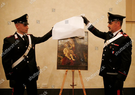 """Italian Carabinieri paramilitary police officers unveil the 15th century painting """"Madonna with Child"""", attributed to Renaissance painter Cima da Conegliano (Gian Battista Cima), during a press conference on recovered paintings seized by the Nazis in 1944 in Camaiore near Lucca, at the Brera Art Gallery, in Milan, Italy, . The paintings were seized from the Italian villa of Prince Felix Bourbon-Parma, then Prince of Luxembourg, and kept by the Supreme Comander of all SS forces Italy Karl Wolff at his residency of the Castle Dornsberg, near Merano, South Tyrol before being sent to Germany. The paintings were found on Dec. 3, 2014 in Milan"""