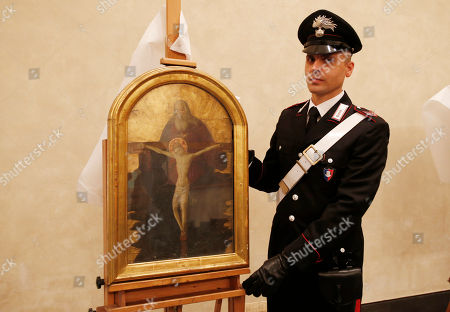 """Italian Carabinieri paramilitary police officer stands next to a painting """"Trinity"""", attributed to early Renaissance painter Alessio Baldovinetti, during a press conference on recovered paintings seized by the Nazis in 1944 in Camaiore near Lucca, Italy, at the Brera Art Gallery, in Milan, Italy, . The paintings were seized from the Italian villa of Prince Felix Bourbon-Parma, then Prince of Luxembourg, and kept by the Supreme Comander of all SS forces Italy Karl Wolff at his residency of the Castle Dornsberg, near Merano, South Tyrol before being sent to Germany. The paintings were found on Dec. 3, 2014 in Milan"""
