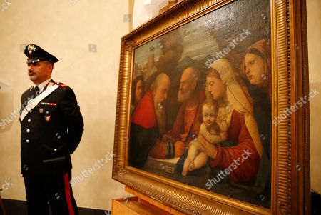 """Italian Carabinieri paramilitary police officer stands next to a painting """"Circumcision of Jesus at Temple"""", attributed to early Renaissance painter Girolamo dai Libri, during a press conference on recovered paintings seized by the Nazis in 1944 in Camaiore near Lucca, Italy, at the Brera Art Gallery, in Milan, Italy, . The paintings were seized from the Italian villa of Prince Felix Bourbon-Parma, then Prince of Luxembourg, and kept by the Supreme Comander of all SS forces Italy Karl Wolff at his residency of the Castle Dornsberg, near Merano, South Tyrol before being sent to Germany. The paintings were found on Dec. 3, 2014 in Milan"""